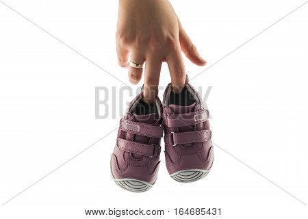 Baby shoes isolated on white background and woman hand