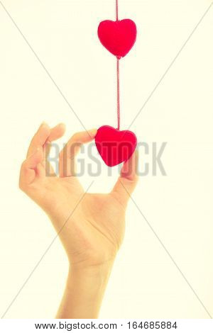Love and help. Smoothy female hand with sign symbol of charity and fondness. Palm with red little hearts.