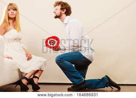 Handsome man giving pretty unhappy bored woman candy bunch flowers. Young boyfriend with present gift kneeling in front of girlfriend.
