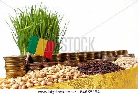 Mali Flag Waving With Stack Of Money Coins And Piles Of Wheat And Rice Seeds