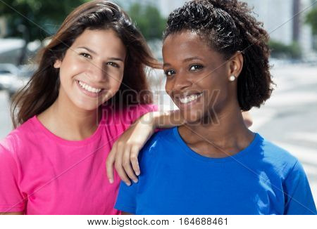 Happy mexican girl with caucasian woman outdoor in the city in the summer