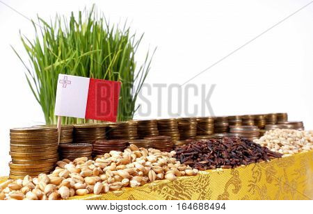 Malta Flag Waving With Stack Of Money Coins And Piles Of Wheat And Rice Seeds