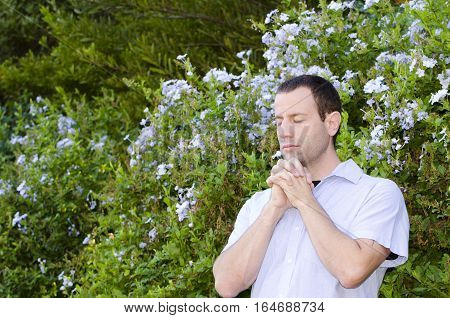Man praying with hands folded in front of a bush with light blue flowers.