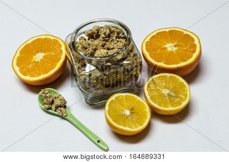 Healty food with jar and spoon of cereals. Orange and lemon are next to cut in half isolated on white background.