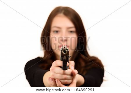 Close up young woman pointing a gun at the camera on white background