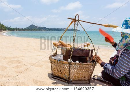 Unidentifiable vendor with a basket on a sandy beach in Thailand. The person is grilling sausages.