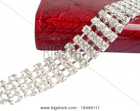 Close up of dimond necklace with beautiful red purse on white