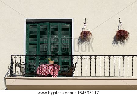 Balcony of old house in traditional Mediterranean style closed door with green shutters two armchairs and table covered with chequered cloth (red and white)