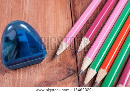 Pencil Sharpener and pencils lying next. Derevyannny background