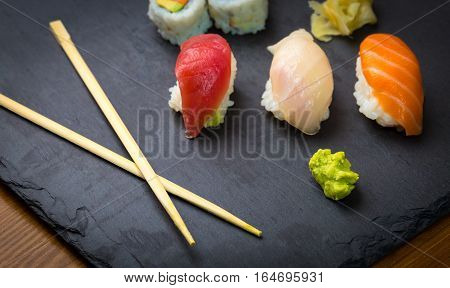 Sushi and Sashimi rolls on a black stone slatter. Fresh made Sushi set with salmon prawns wasabi and ginger. Traditional Japanese cuisine.