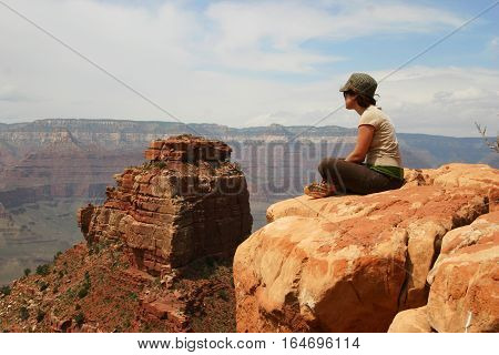 Girl Sitting Cross-Legged Overlooking the Grand Canyon
