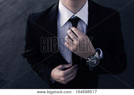 A Well dressed man fixing his tie