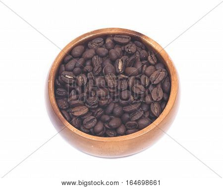 Organic medium dark roasted coffee beans in wooden bowl isolated on white background