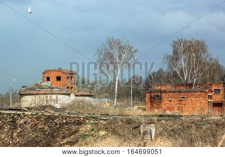 Spring landscape with abandoned destroyed technical brick buildings under the blue sky.