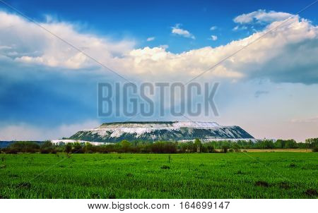 Summer landscape with green field and beautiful cumulus clouds over the white gypsum mountain. Russia Moscow region Voskresensky district.