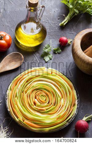 Preparing vegetable pie with ingredients on black background