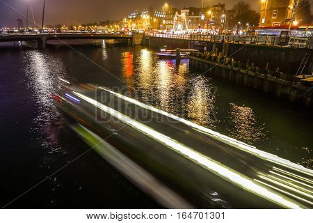 AMSTERDAM NETHERLANDS - JANUARY 02 2017: Cruise boat in night canals of Amsterdam. January 02 2017 in Amsterdam - Netherland.