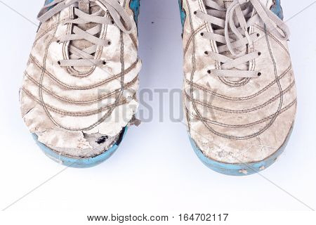 Old damaged futsal sports shoes  on white background  isolated close up
