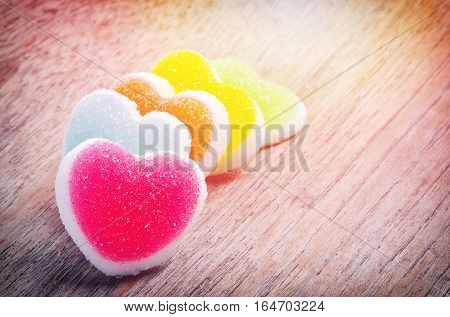 Colorful of jelly candy with heart sign on wooden background.
