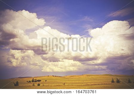 Beautiful cloudscape over rolling green hills and farmland in the New South Wales countryside, Australia. Retro toned image.