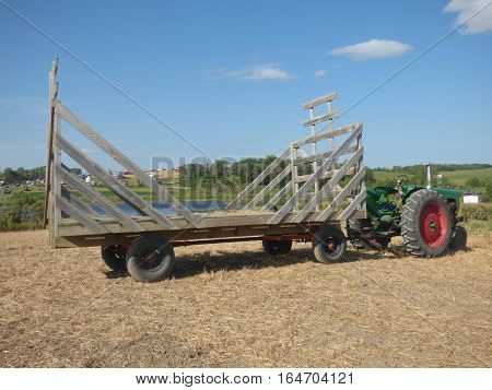 A old style hayrack hooked to a tractor ready to be loaded  with feed for animals.