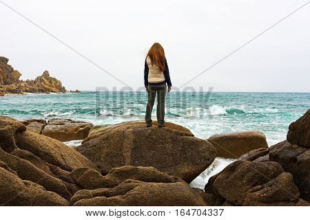 Depressed woman staring into the distance. Girl standing on rock