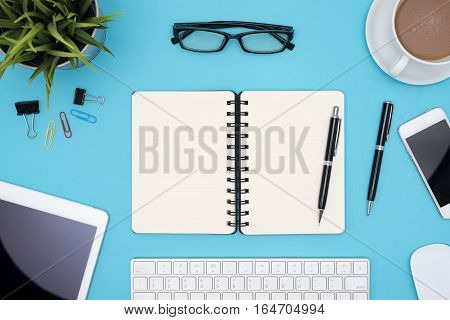 Open blank spiral notebook with office supplies notebook pen pencil tablet phone flower eye glasses and coffee cup on blue desk table Top view with copy space