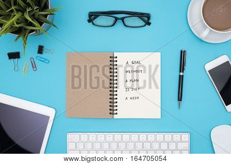 a goal without a plan is just a wish motivational handwriting on spiral notebook with computer office supplies eye glasses and coffee over blue desk table Top view with copy space