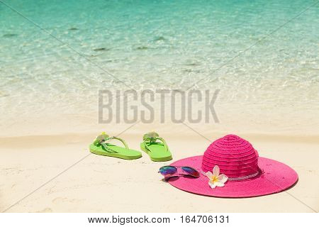 Large pink beach hat sunglasses and green slippers in the golden sand by sea shore