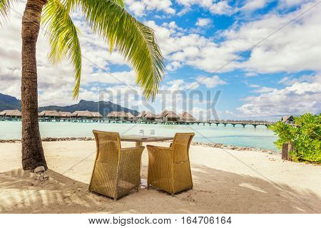 Two chairs and table on a sand beach with a view on the lagoon and Mount Otemanu on the tropical island of Bora Bora near Tahiti in French Polynesia.
