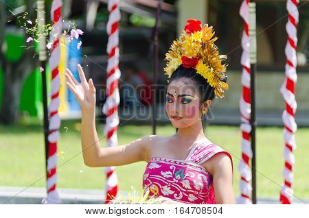 Bali Indonesia - 22 July 2016: A Balinese dancer performs a welcome dance throwing flowers in the air