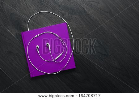 The Purple Book And White Headphones