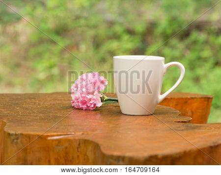 White cup of hot coffee with pink carnation flower on wood table in natural green background in morning.