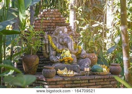 Religious stone sculpture of Ganesha god in garden Thailand. Sculpture/symbols of Buddhism.