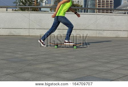 young skateboarder legs riding skateboard at city