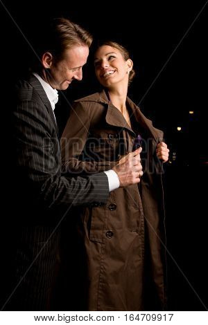 man helping his girlfriend put on her coat