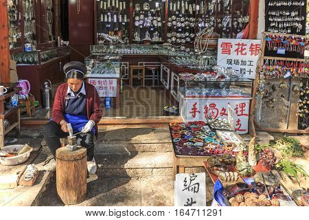 Lijiang, China - November 14, 2016: Young Naxi Man Working On His Workshop In Lijiang Old Town