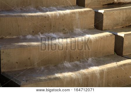 Modern fountain with waterfall. The stream flowing through the steps in the Garden Jesuit in old town Kutna Hora, Czech Republic, Czechia.