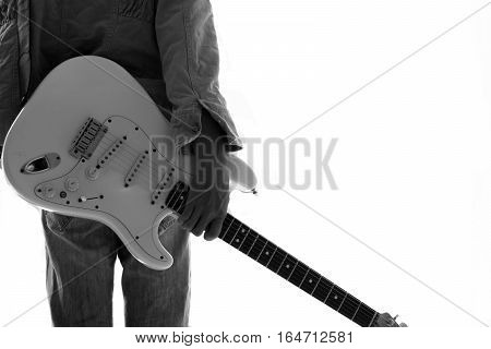 A young man with an electric guitar Leaning against a cement wall Happy and relaxed Waiting for the show.
