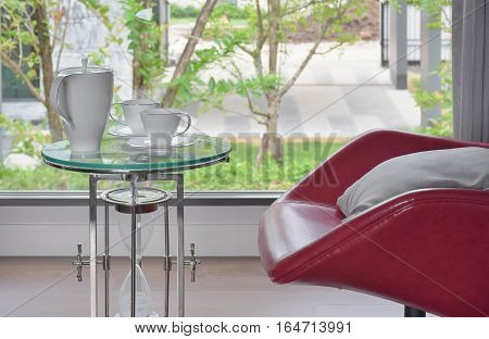 Tea Set On Glass Top Table With Red Easy Chair In Living Room