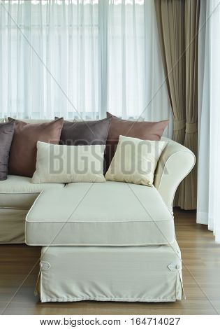 L Shape Beige Sofa With Varies Brown Color Of Pillows