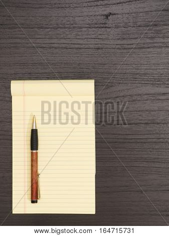Dark Wood Desk Yellow Notepad Ballpoint Pen