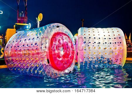water ball to entertain children in an amusement park at night under a thousand colors of the lights of the games