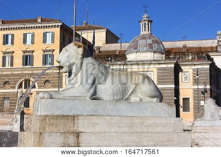 one of the four fountains in the form of a lying lion, around the egyptian obelisk of Ramesses II from Heliopolis stands in the centre of the Piazza del Popolo, Rome, Italy