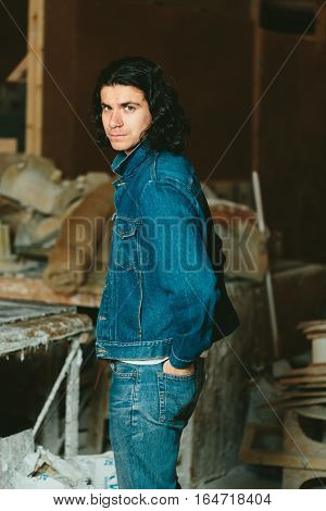 Young handsome man with long hair brunette in a denim jacket