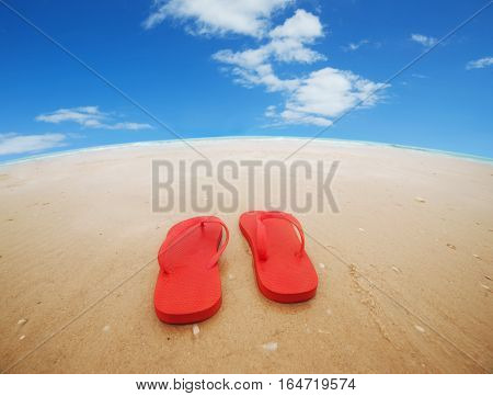 Red flip flops on the beach.Concept of summer vacations.Wide angle