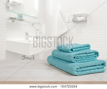 Turquoise spa towels pile on wood over blurred bathroom background