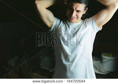 Beautiful long-haired brunette guy hands behind his head in white t-shirts