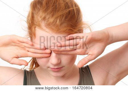 Portrait of a teenage girl covering her eyes on white background