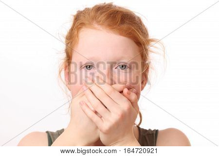 Portrait of a surprised looking teenage girl covering her mouth with hands on white background